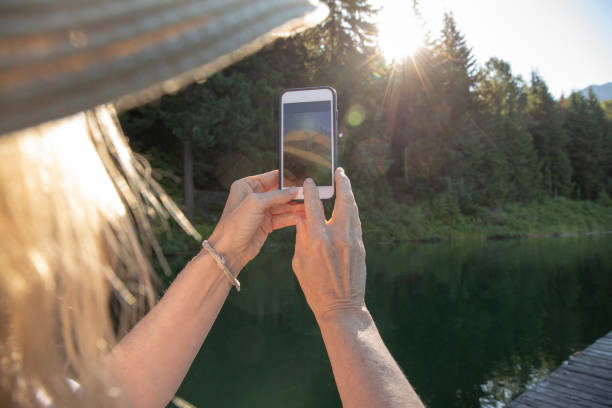 Portrait of a woman taking a photo with mobile phone of the sun rise through the distant forest