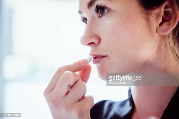 portrait of a woman taking a pill of medicine. - medicijnen innemen stockfoto's en -beelden
