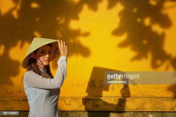 portrait of a woman touching her hat, vietnam - vietnamese cultuur stockfoto's en -beelden