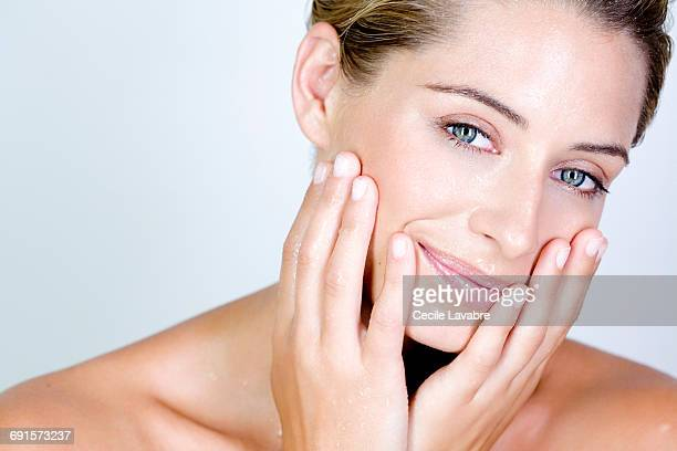 Portrait of a woman touching her wet face