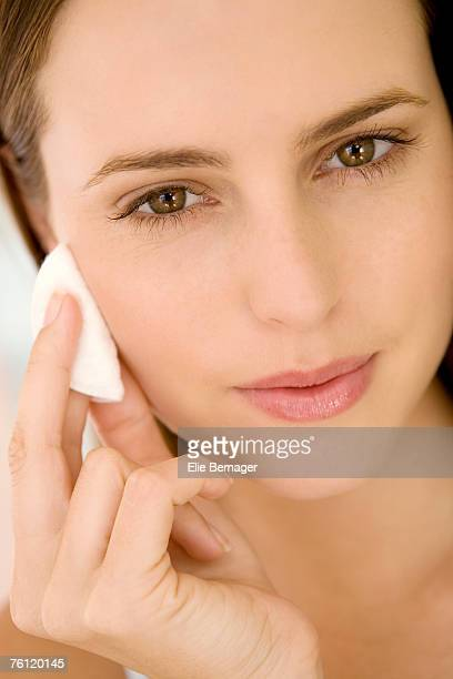 Portrait of a woman using a cleansing cotton on her cheek, indoors