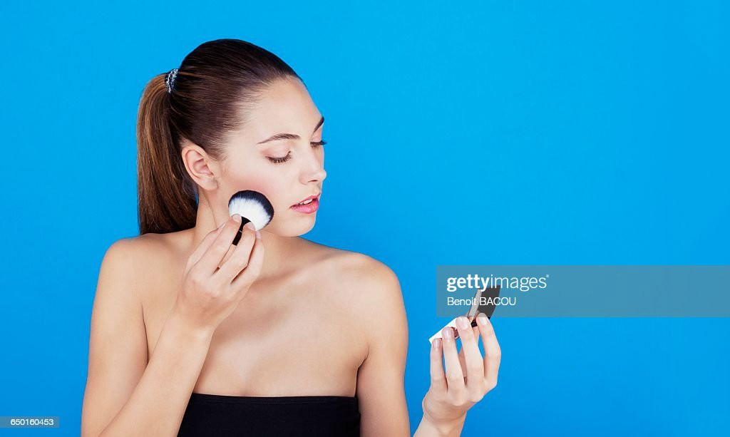 Portrait of a woman using make-up brush on face : Stock Photo
