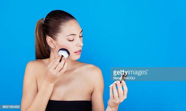 Portrait of a woman using make-up brush on face
