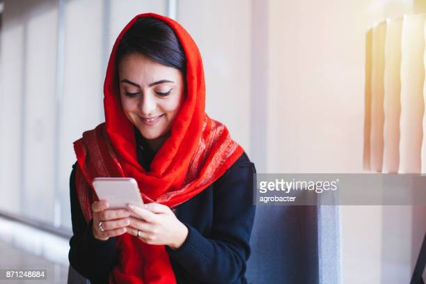 portrait of a woman using smartphone - iranian woman stock photos and pictures
