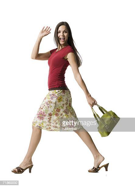 portrait of a woman walking with a purse - striding stock pictures, royalty-free photos & images
