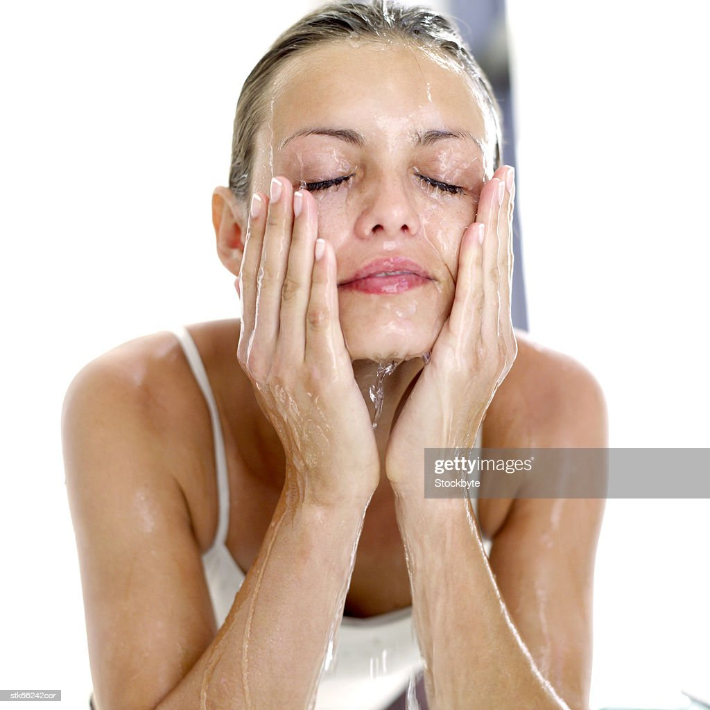 portrait of a woman washing her face with water : Stock Photo