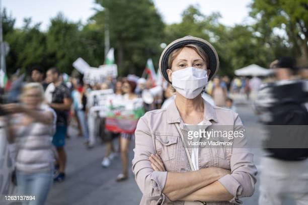 porträt einer frau, die eine gesichtsmaske vor einer menschenmenge trägt, die für ihre rechte demonstriert - demonstration stock-fotos und bilder