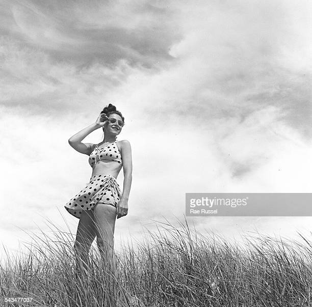 Portrait of a woman wearing a polka dot bathing suit and standing among the plants on the beach Provincetown Massachusetts 1948