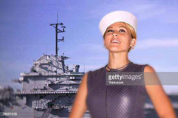 Portrait of a woman wearing a sailor hat with an American aircraft carrier behind her.