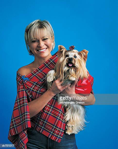 portrait of a woman wearing a tartan shawl holding a yorkshire terrier - shawl stock pictures, royalty-free photos & images