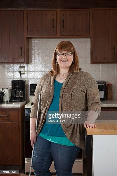 Portrait of a woman who is legally blind with her cane in her kitchen
