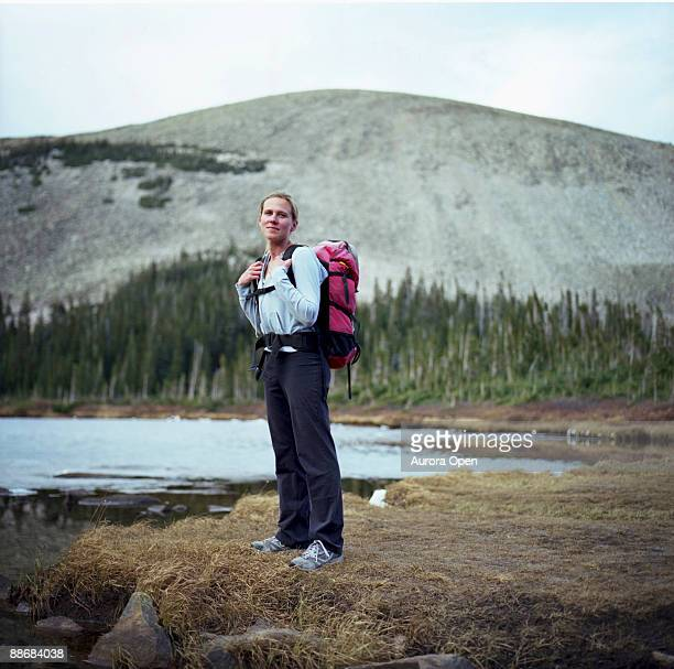 a portrait of a woman with a backpack standing near a lake and a mountain in the background, colorado. - open backpack stock pictures, royalty-free photos & images