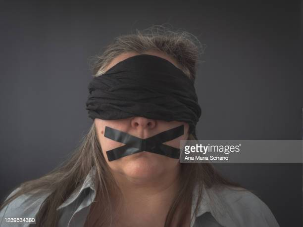portrait of a woman with a black blindfold covering her eyes and an x of adhesive tape covering her mouth - fascism stock pictures, royalty-free photos & images