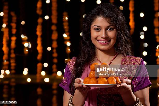 portrait of a woman with a plate of sweets - mithai stock pictures, royalty-free photos & images