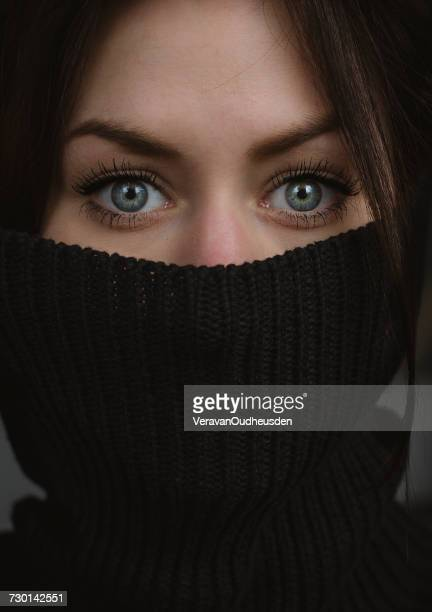Portrait of a woman with a turtleneck jumper covering her mouth