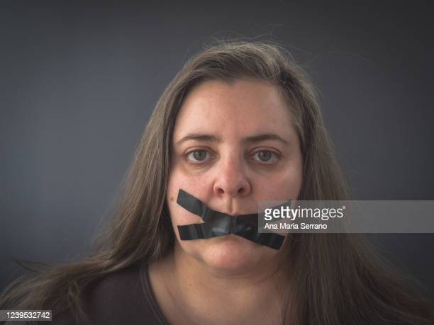 portrait of a woman with an x of adhesive tape covering her mouth - fascism stock pictures, royalty-free photos & images