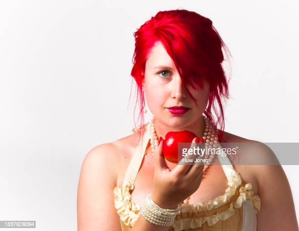 portrait of a woman with bright red hair with a red apple - only young women stock pictures, royalty-free photos & images
