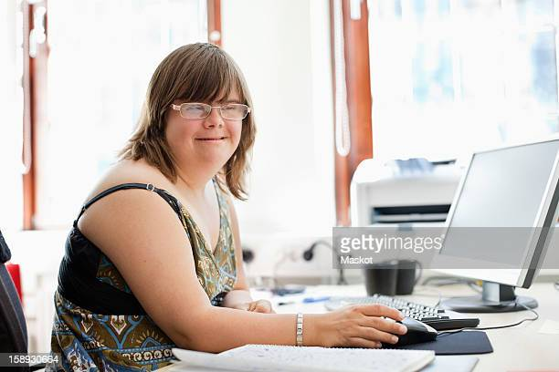 Portrait of a woman with down syndrome using computer at office