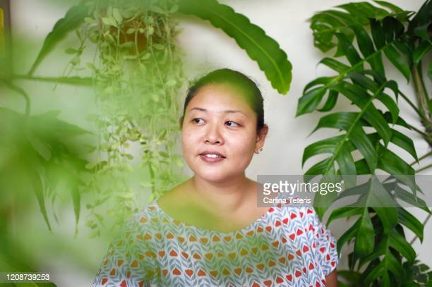 portrait of a woman with her houseplants - showus stock pictures, royalty-free photos & images