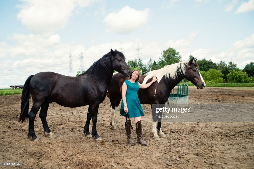 Portrait of a woman with horses in a shelter. : Stock Photo
