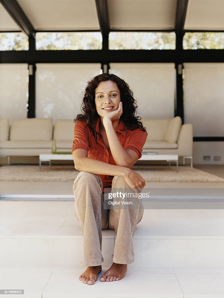 Portrait of a Woman with Long Brown Hair Sitting in a Modern Living Room : Stock Photo