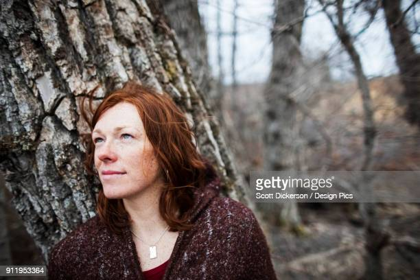 portrait of a woman with red hair against a tree and looking contemplative - home run ストックフォトと画像