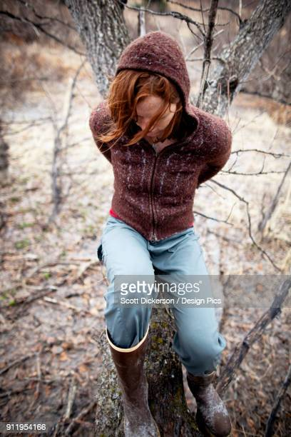 portrait of a woman with red hair leaning on a cottonwood tree and looking contemplative - home run ストックフォトと画像