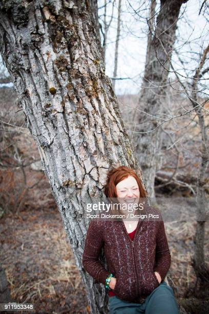 portrait of a woman with red hair leaning on a tree and laughing with eyes closed - home run ストックフォトと画像