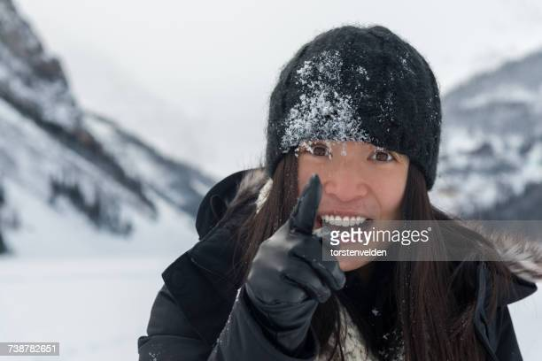 Portrait of a woman with snow on her face pointing her finger, Lake Louise, Alberta, Canada