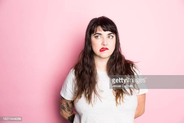 portrait of a woman with tattoos and red lipstick against a pink background - confusion stock pictures, royalty-free photos & images