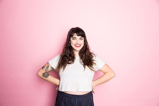 Portrait of a Woman with tattoos and red lipstick against a pink background - gettyimageskorea