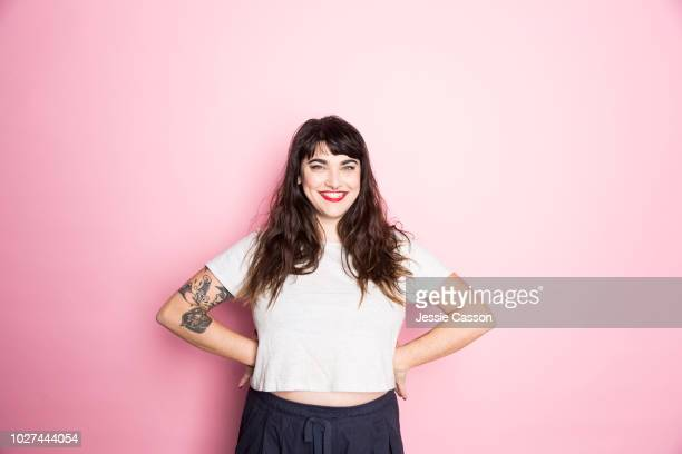 portrait of a woman with tattoos and red lipstick against a pink background - volwassen vrouwen stockfoto's en -beelden