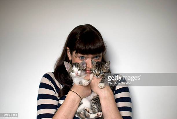 Portrait of a woman with two kittens
