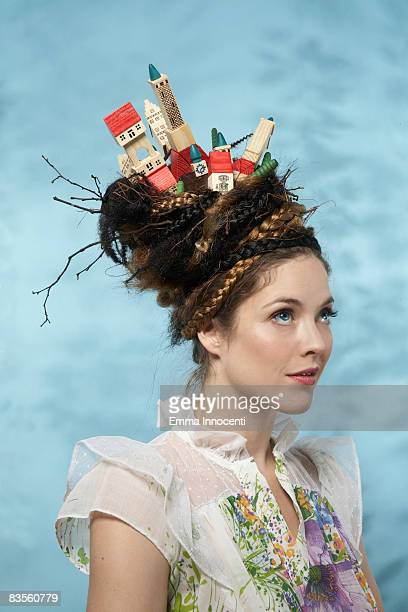 Portrait of a woman with wooden houses on her head