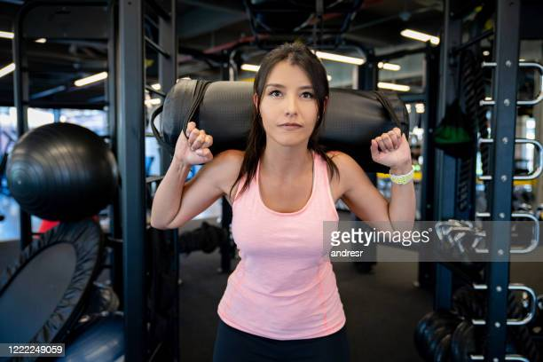 portrait of a woman working out at the gym doing squats with a sand bag - sandbag stock pictures, royalty-free photos & images