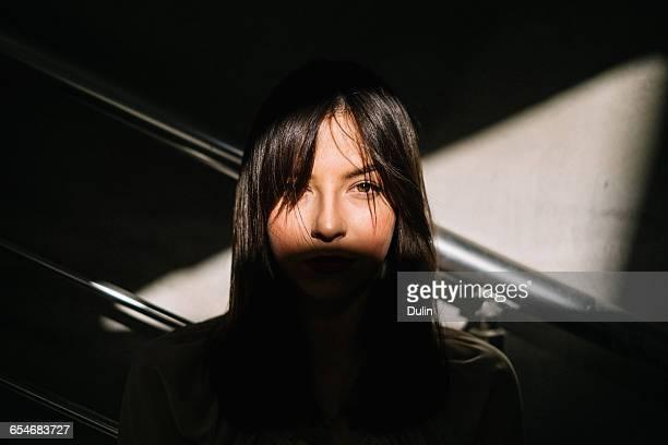 portrait of a woman's face in shadow - schlagschatten stock-fotos und bilder