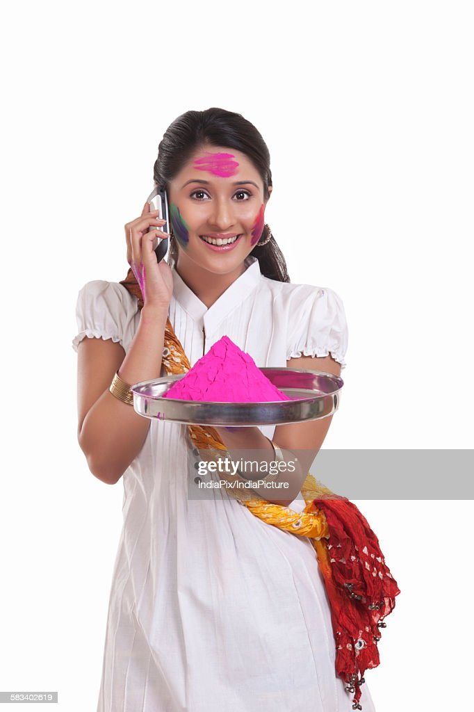 Portrait of a WOMEN with holi colour talking on a mobile phone : Stock Photo