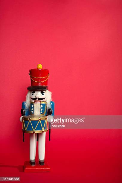 Portrait of a wooden nutcracker on light red background