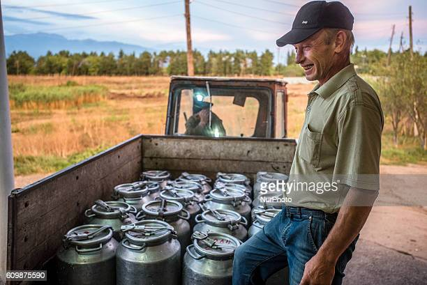 Portrait of a worker delivering milk cans from cowsheds to the dairy factory at the Nikitin Kolkhoz in Ivanovka village Azerbaijan Dairy products of...
