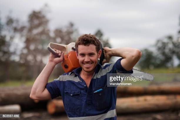 Portrait of a worker holding a chainsaw at a sawmill