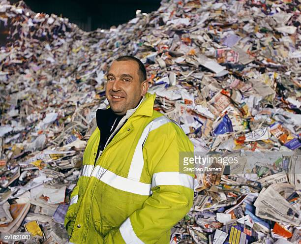 Portrait of a Workman in a Fluorescent Jacket Standing in Front of a Pile of Paper for Recycling
