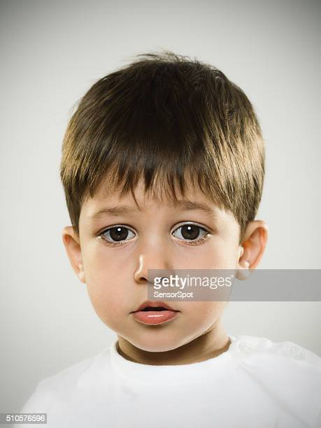 Portrait of a worried kid looking at camera.