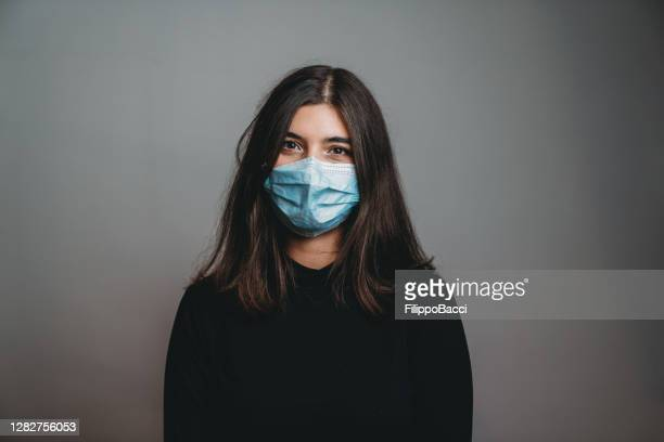 portrait of a young adult beautiful woman looking at camera wearing a protective face mask - brown eyes stock pictures, royalty-free photos & images
