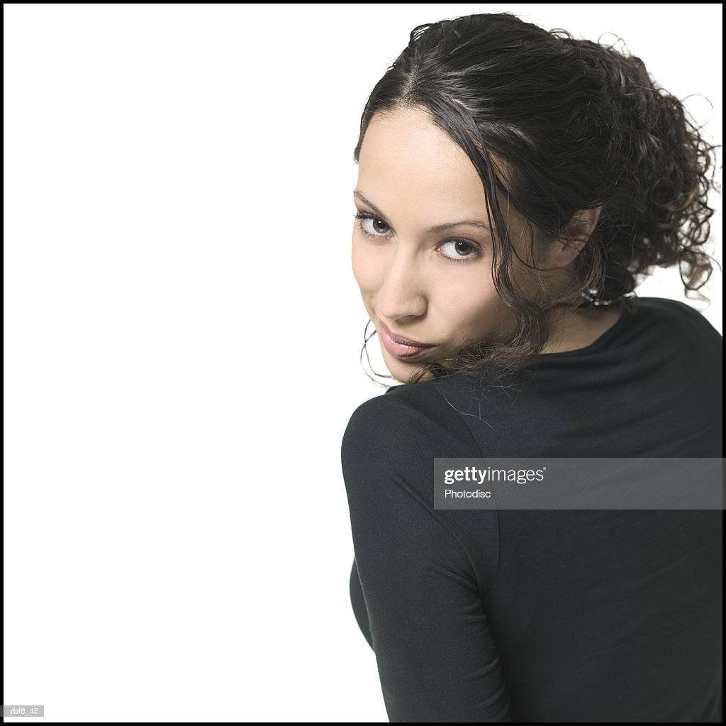 portrait of a young adult brunette female in a black shirt as she turns around and grins slightly : Stock Photo