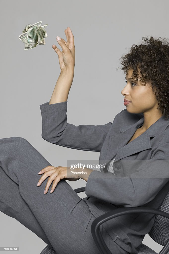 portrait of a young adult business woman as she throws away a wad of cash : Foto de stock