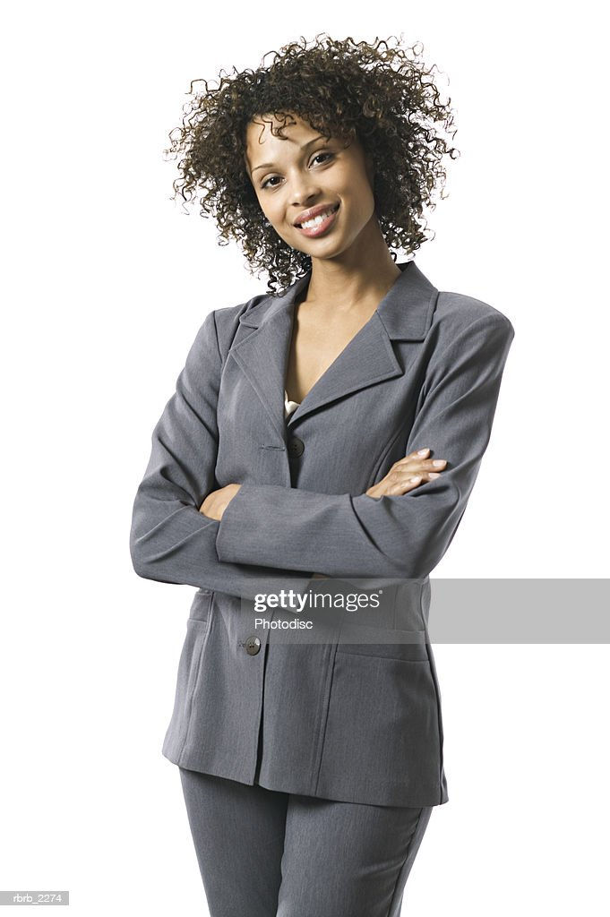 portrait of a young adult business woman in a grey suit as she folds her arms and smiles : Foto de stock