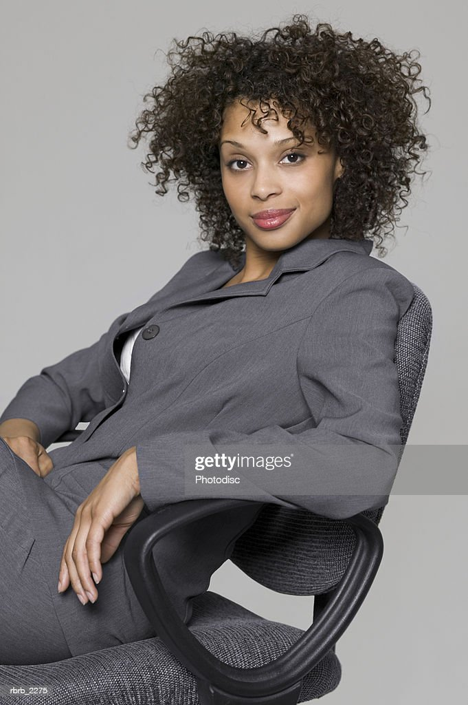 portrait of a young adult business woman in a grey suit as she sits in a chair and smiles : Foto de stock