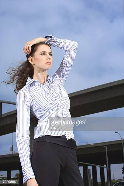portrait of a young adult businesswoman by the elevated roads, low angle view, three quarter length - three quarter length ストックフォトと画像