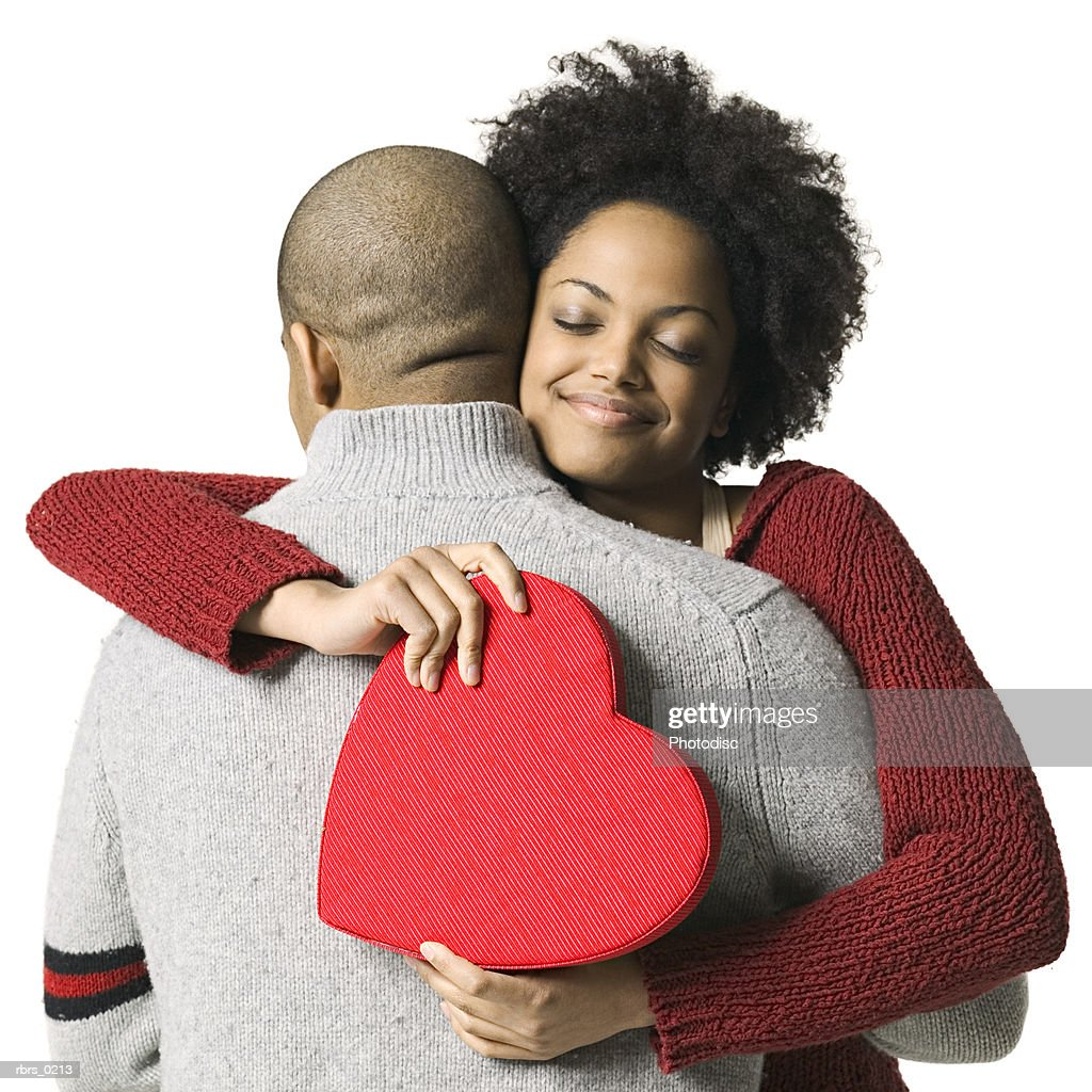 portrait of a young adult couple as the girl hugs her boyfriend after getting a valentines gift : Foto de stock