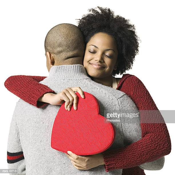 portrait of a young adult couple as the girl hugs her boyfriend after getting a valentines gift - valentines african american stock pictures, royalty-free photos & images
